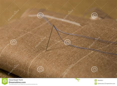 upholstery needle and thread needle and thread on fabric background royalty free stock