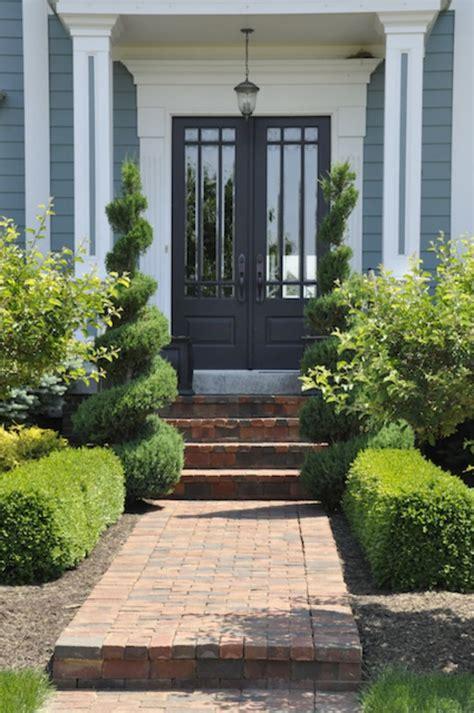 landscaping walkway to front door ornate shrubs and a brick walkway make this front door