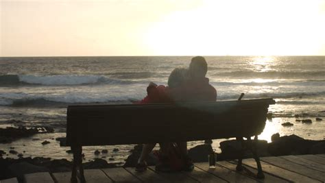bench couple watch a man and woman sit in a beach chair in the sand watching