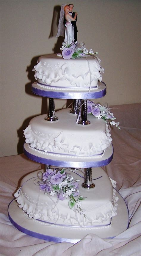 shaped cake 3 tier heart shaped cake on pillars with gumpaste flowers