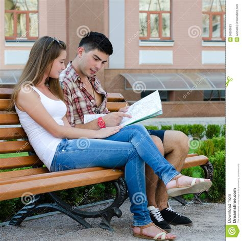 couple sitting on bench young couple sitting on a bench reading a map stock photos