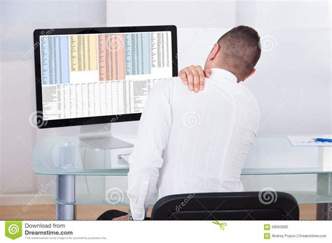 shoulder pain from sitting at desk businessman with shoulder pain using computer stock photo