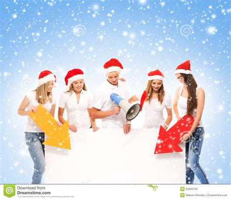 a group of teenagers in christmas hats pointing on a