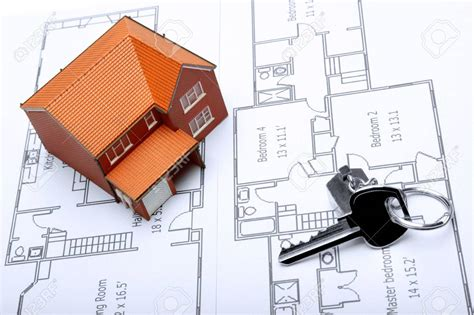 a model home and house key on architectural floor plans