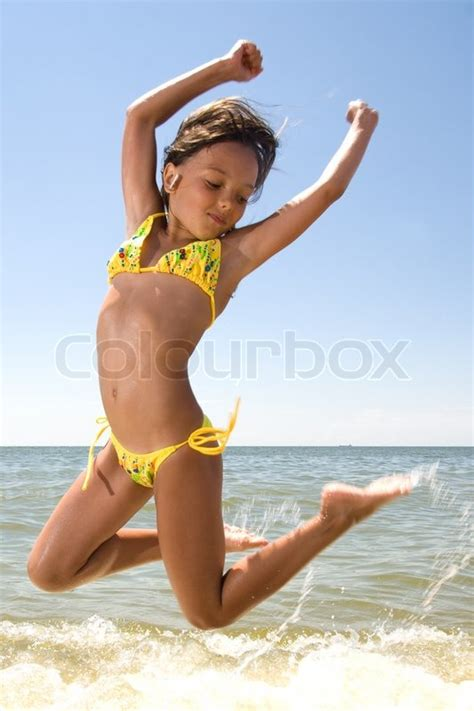very young little girl 13y little girl jumping at the sea stock photo colourbox