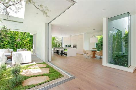 House with multilevel decks surrounded by gardens