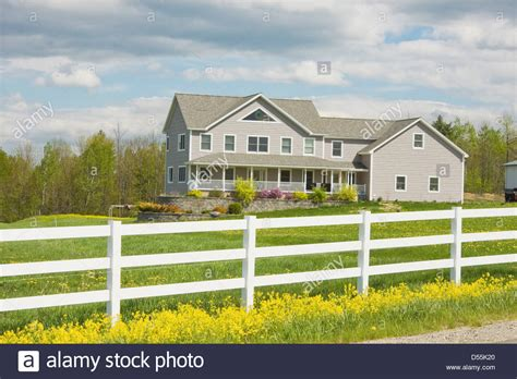 two farmhouse two farmhouse style home and white fence in rural