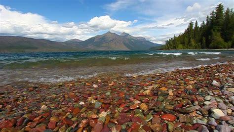lake mcdonald montana colored rocks waves crash through bright glacial rocks of lake mcdonald