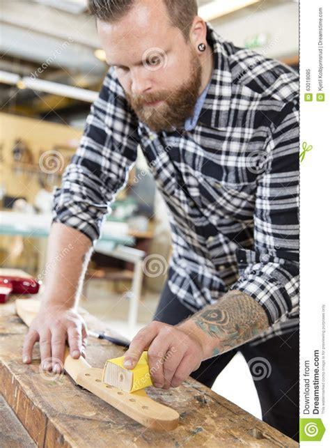 carpenter sanding a guitar neck in wood at workshop stock
