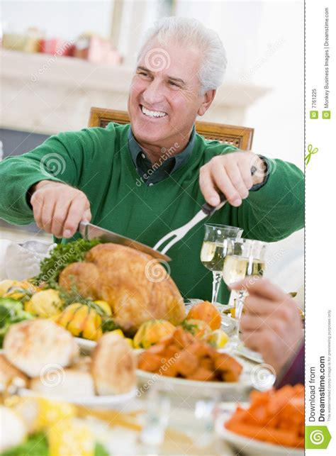 man carving up turkey at christmas dinner royalty free