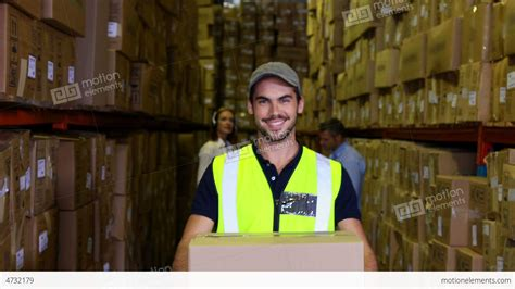 warehouse worker smiling at carrying a box stock