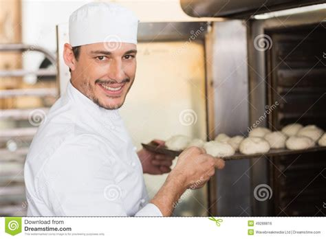 Oven The Baker smiling baker putting dough in oven stock photo image