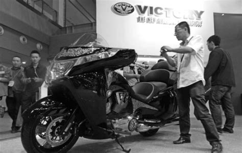 man takes photo   victory branded motorcycle