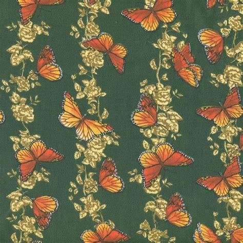 orange monarch butterflies on green cotton fabric bty