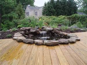 Waterfall pond with wood stained deck contemporary patio dc