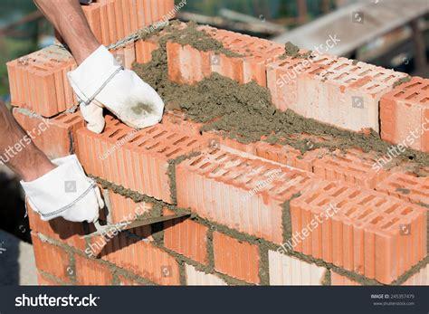 bricklayer worker installing blocks caulking stock