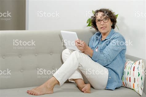 mature sofa mature woman with a tablet on the sofa stock photo