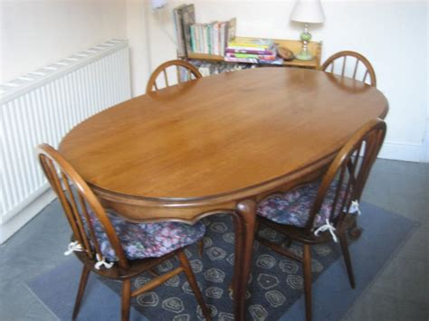 set of ercol chairs and oval solid wood dining table for