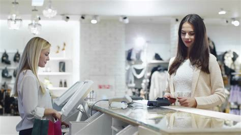 Uhd Cashier S Office is paying with smartphone application at the desk in a department store