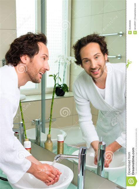 men in the bathroom young man in bathrobe in hotel bathroom stock photo