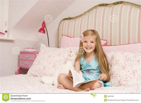 girl sitting on bed young girl sitting on bed with book smiling royalty free