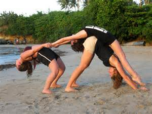 Three women perform a yoga move on the beach in dominican republic