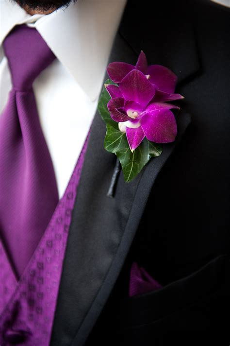 groomsman wearing black suit  purple vest  tie  purple  green floral boutonniere