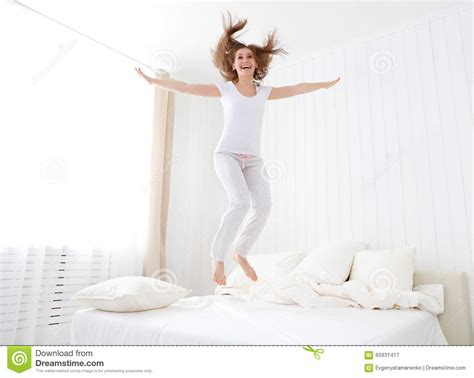 how to make a woman happy in bed happy girl jumping and having fun in bed stock photo