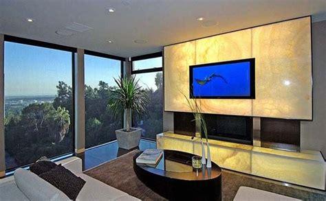 backlit onyx panels surrounding  wall mounted tv visit