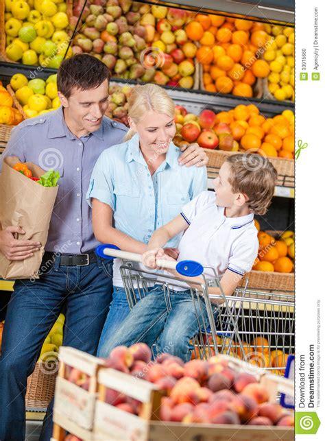 Shelf Of Oranges by Family Against Shelves Of Fruits Goes Shopping Stock Photo