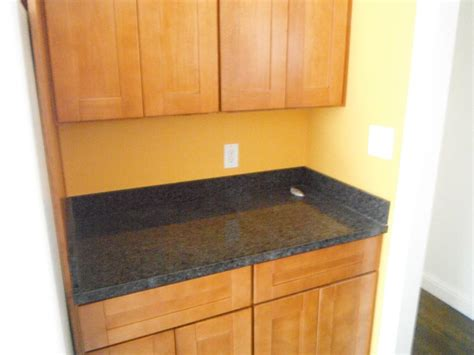 Grey solid surface counter top with backsplash stocker tile