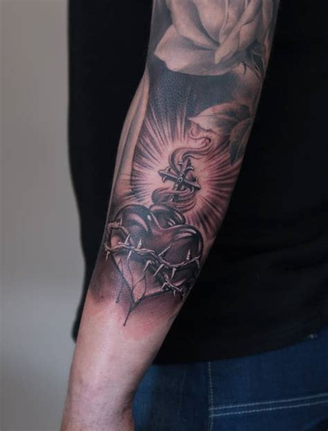 grey sacred heart tattoo on left arm by henrik nissen