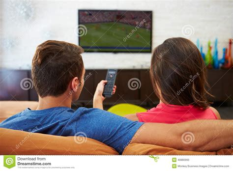 sofa for watching tv rear view of couple sitting on sofa watching tv together