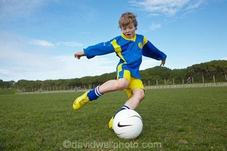 young boy kicking football