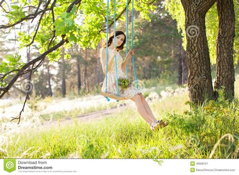 swinging on a swing young beautiful woman is swinging on a swing in summer