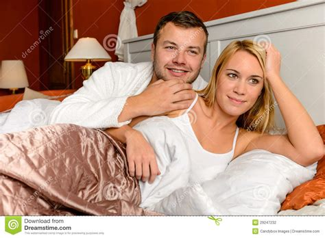 smiling husband holding lying bed married stock