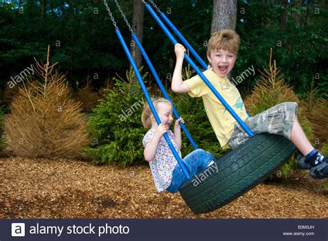 swing for 3 year old 3 year old girl and 6 year old boy on tire swing stock