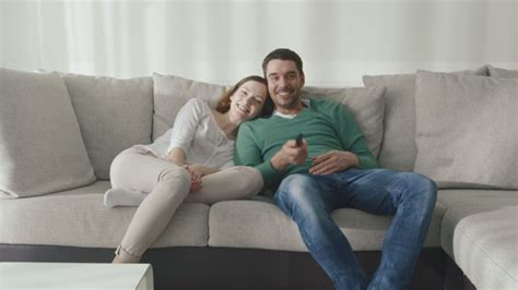 people having on the couch couple is sitting on the couch at home and watching tv by