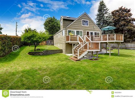 house with a big backyard brown walkout deck with white trim backyard view stock