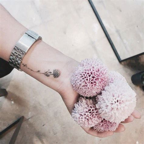 small pompon dahlia tattoo on the left wrist