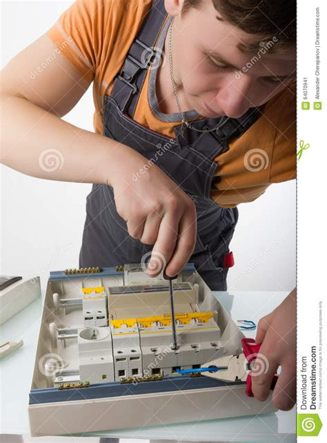 domestic electrician electrician fixing cable in domestic electrical box stock