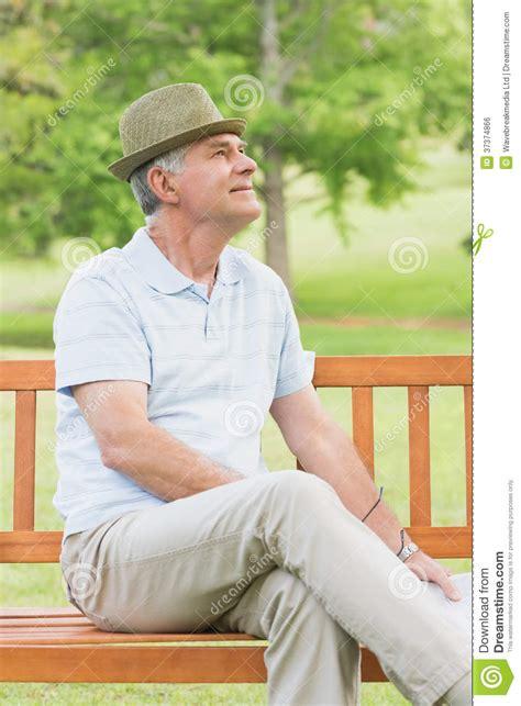 guy sitting on bench senior man sitting on bench at park royalty free stock