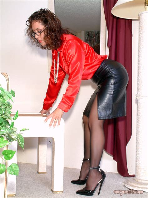 Mature Girl Posing In A Black Leather Skirt And Red Jacket