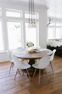 Round salvaged wood dining table lined with eames molded plastic