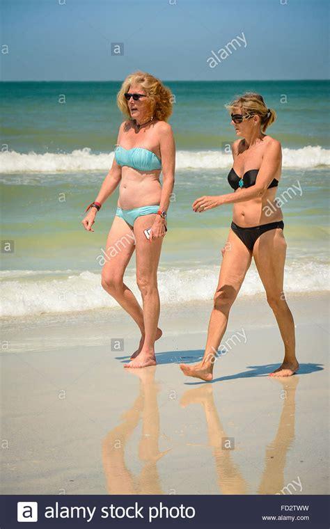 swimwear for middle aged women two older middle aged women in bikinis stroll the beach