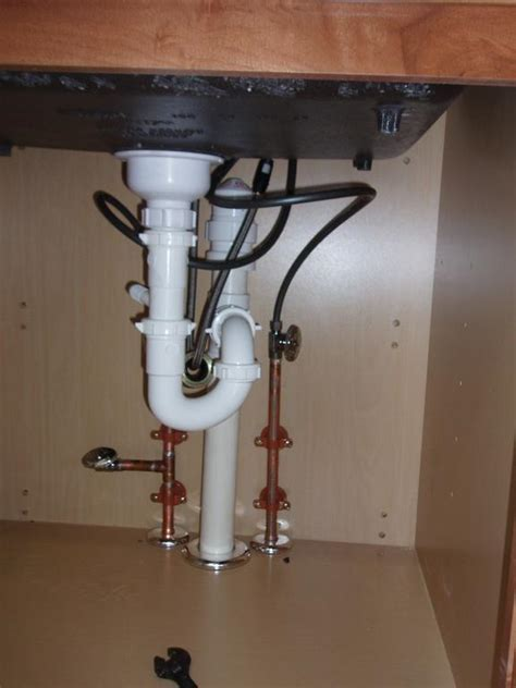 Newly installed kitchen sink drain and water lines from