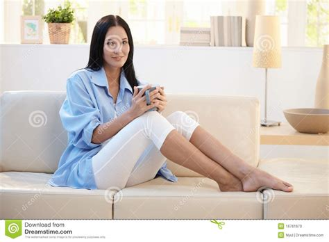 having on couch portrait of smiling woman having coffee on sofa stock