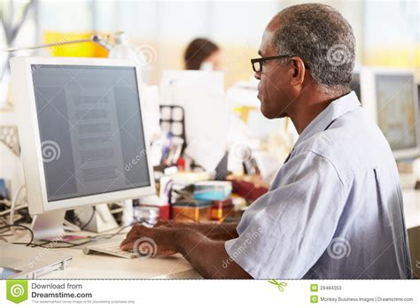 mens office desk man working at desk in busy creative office stock photo