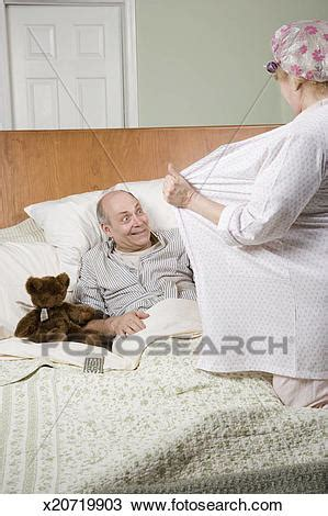 women undressing in bedroom stock photo of woman undressing in front of man in bed
