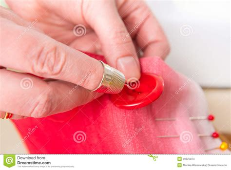 sewing upholstery by hand hand sewing button on fabric stock photo image 39427074